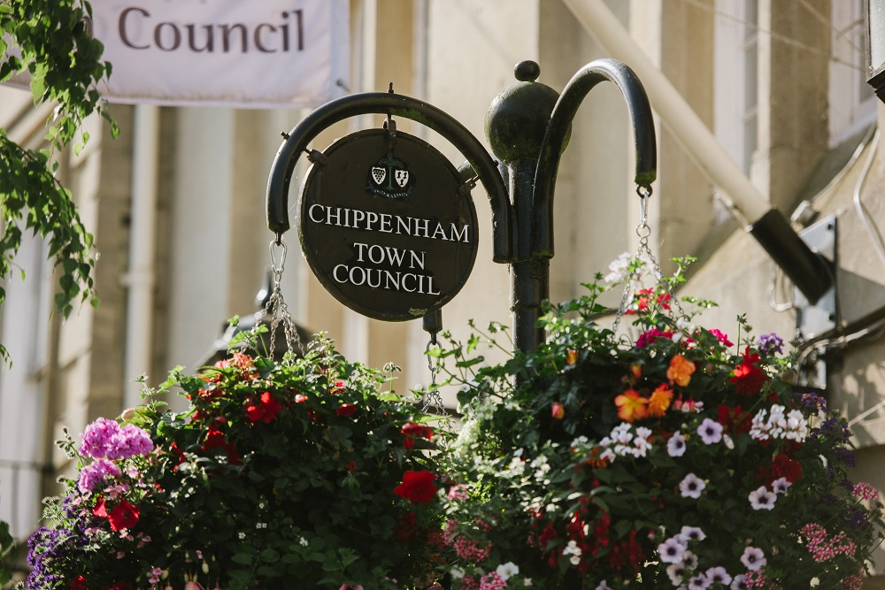 Black Chippenham Town Council sign with white writing and hanging baskets, flowers in bloom, white Council flag in the background.