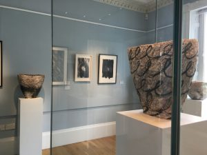 Exhibition of ceramic vessels on white plinths and framed drawings on blue walls