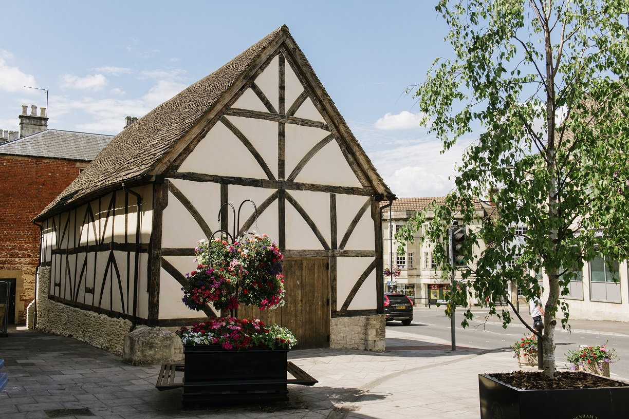 Yelde Hall Chippenham. White and black building with large wooden door. Tall green tree and flower display outside.