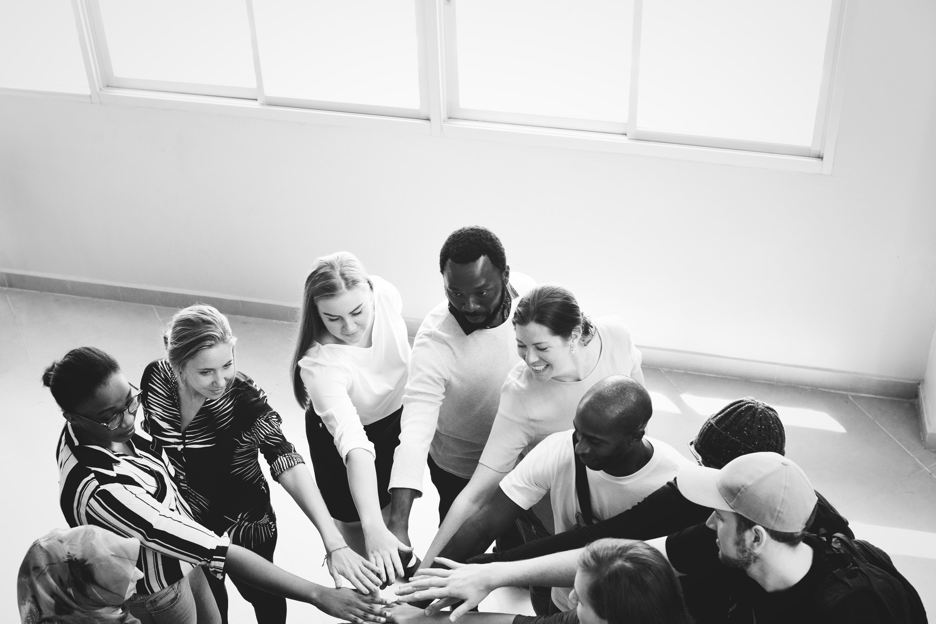 A black and white image of a group of people all stood in a circle with their hands piled on top of each other.