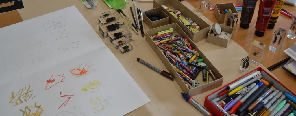 table covered in craft materials including pens, paper and crayons
