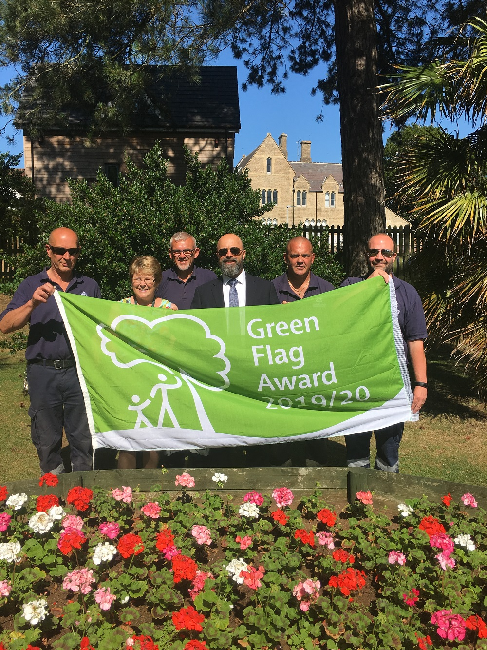 Members of Chippenham Town Council standing behind a large green flag with white writing saying 'Green Flag Award 2019-2020'. Sunny blue sky with trees behind the people and colourful flowers in front.