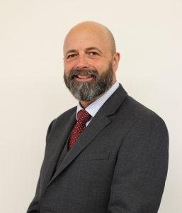 Chief Executive, Mark Smith, red tie, grey suit.
