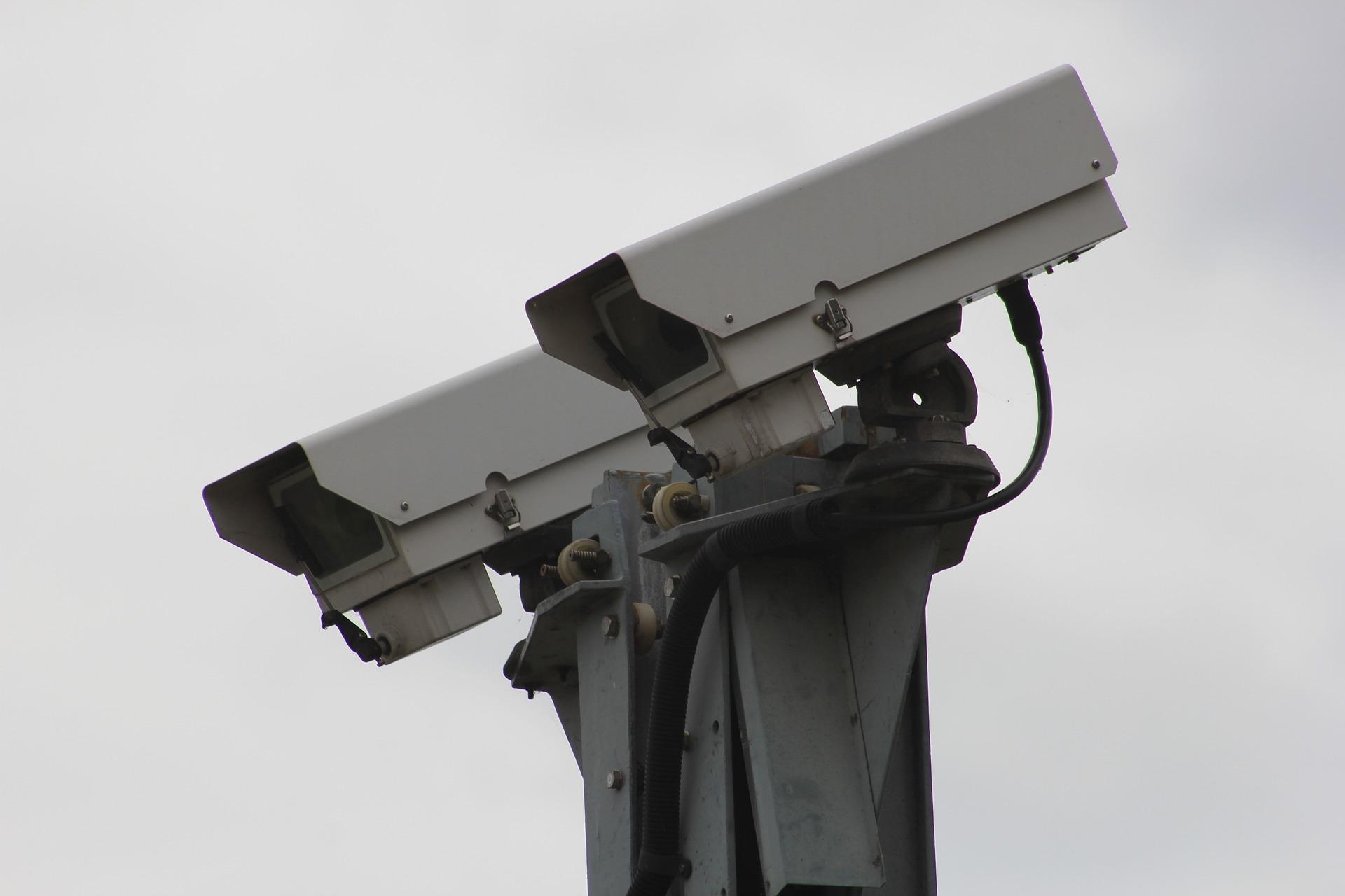 two grey metal CCTV cameras