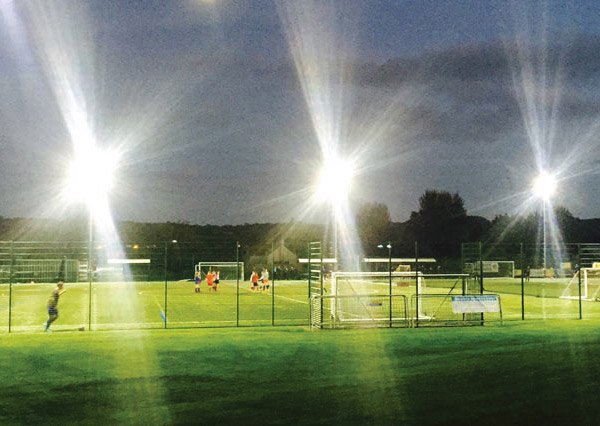 Green outdoor football pitches, bright flood lights, people playing football