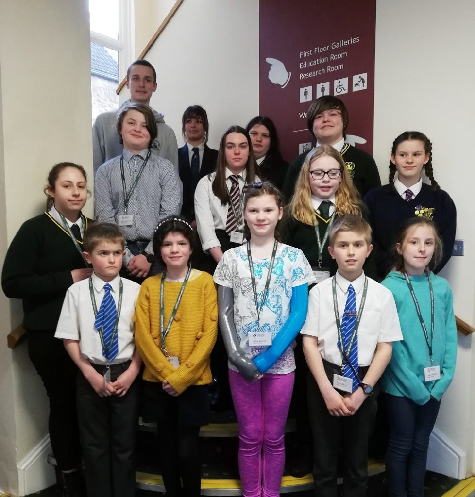 Members of Chippenham Youth Council, standing on stairs, wearing green Chippenham Town Council lanyards