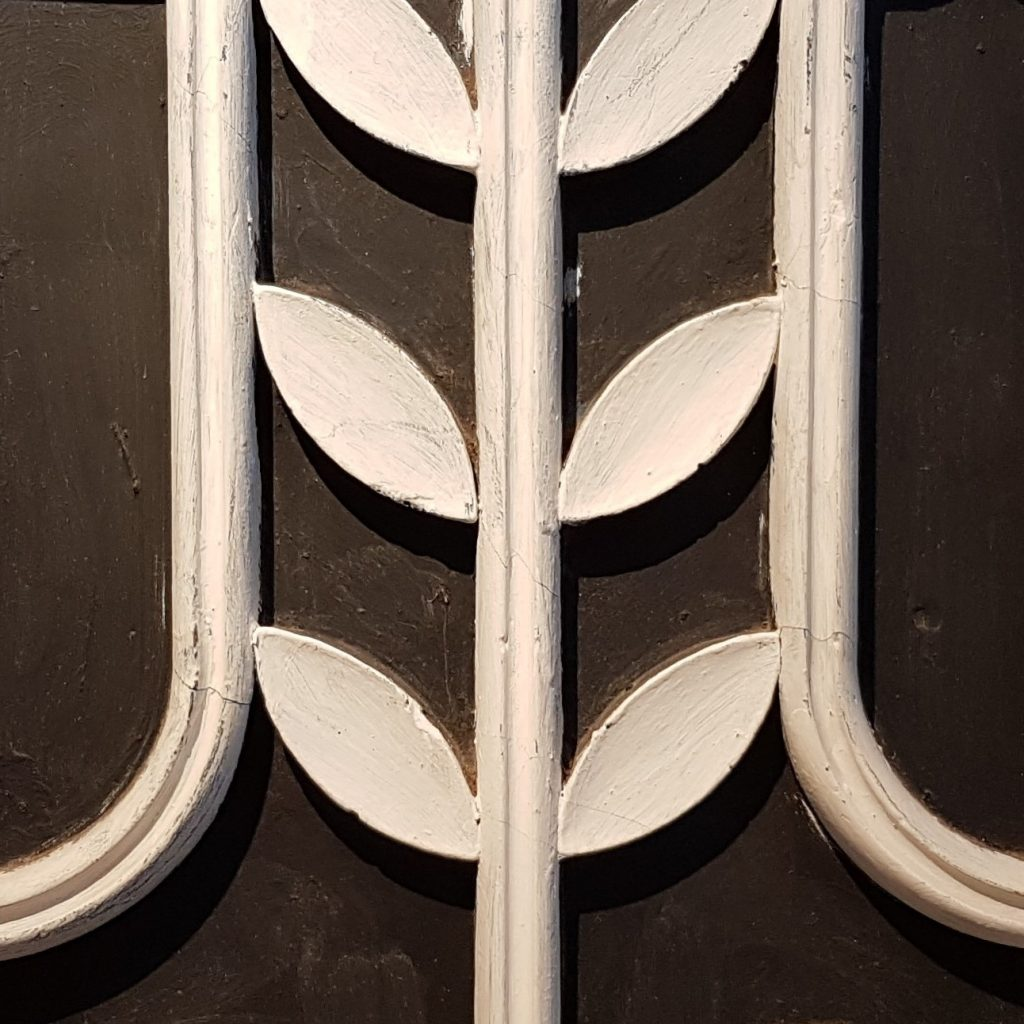 close up of plaster panels, showing six white symmetrical leaves against a black background