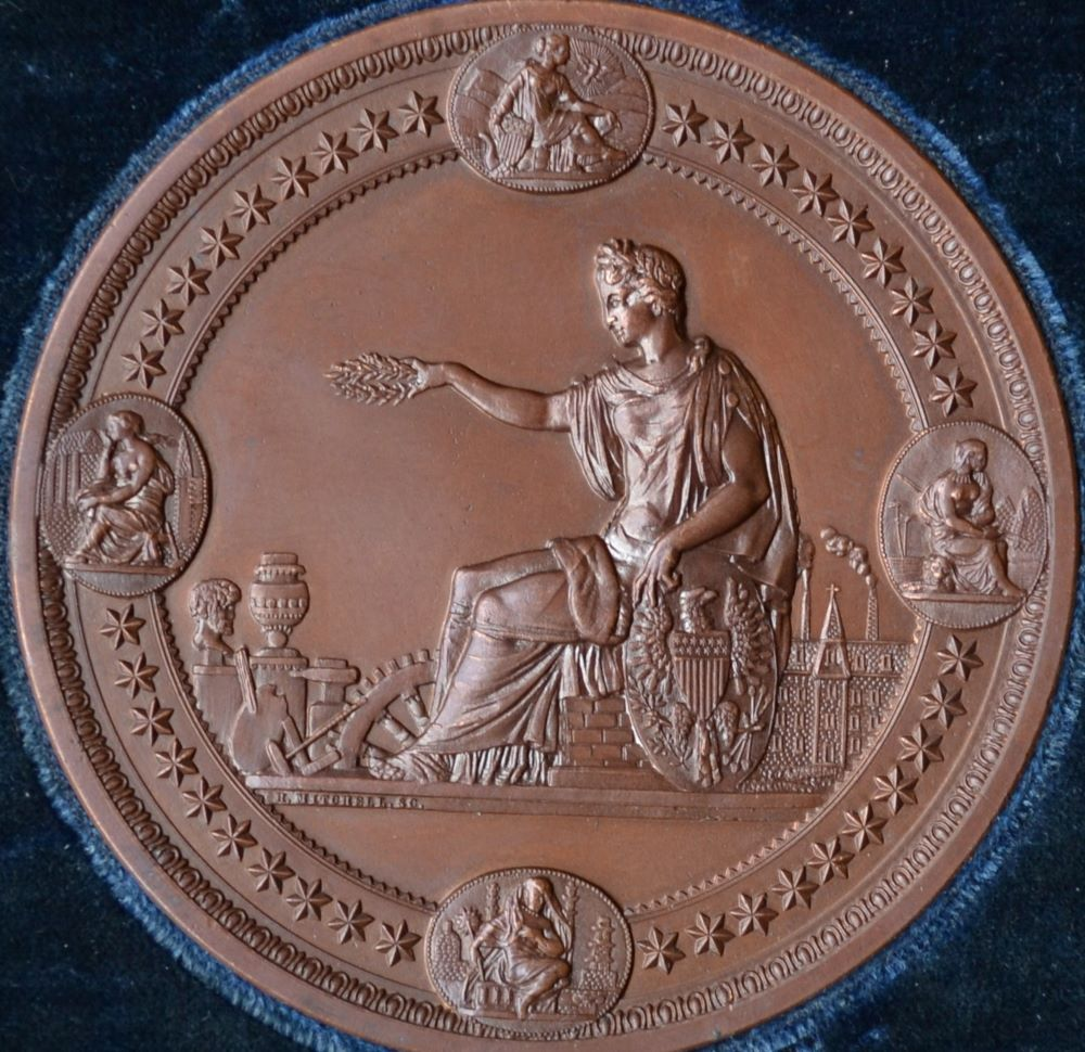 circular bronze medal with a seated classical figure presenting a laurel wreath