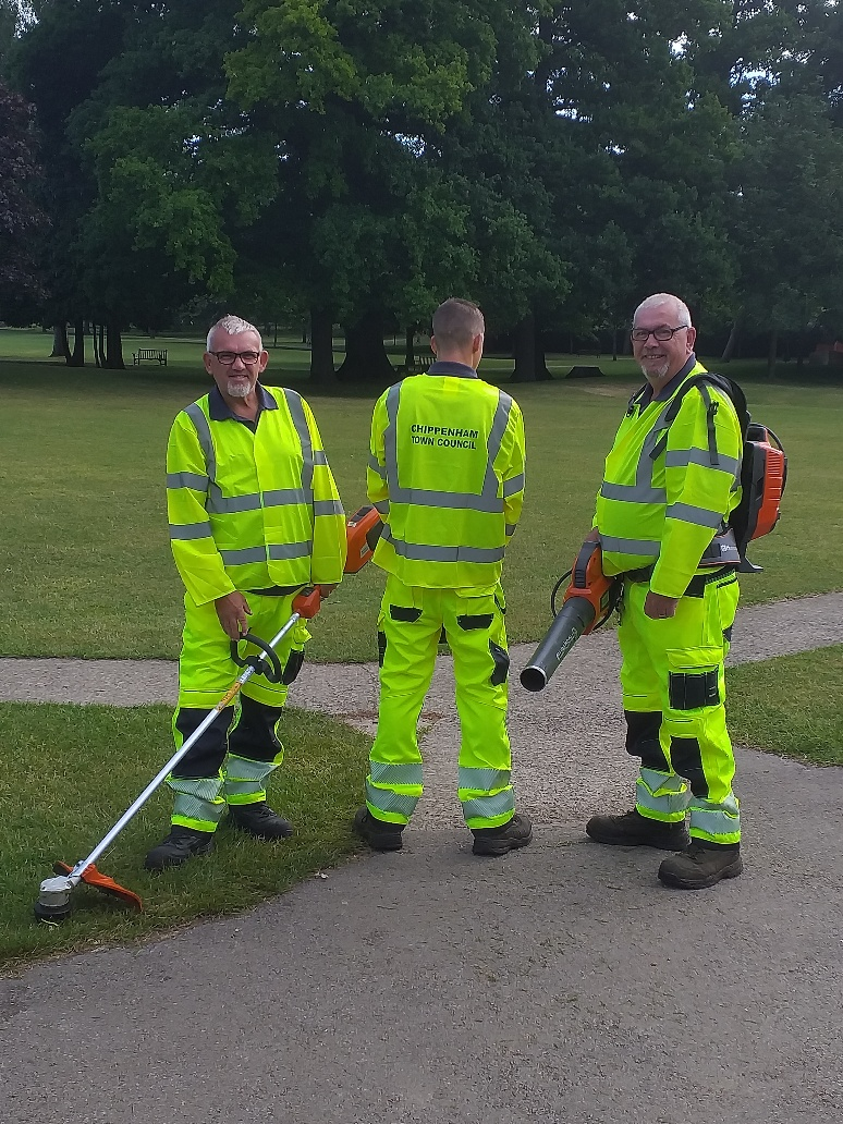 Three members of the Environmental Services team , wearing yellow high visibility clothing, holding outdoor machinery