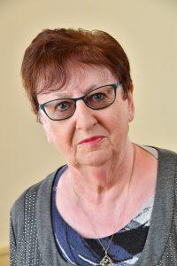 Councillor Densa Allen, glasses, blue top, grey jumper, gold necklace