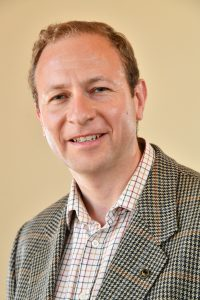Councillor James Adman, green red and yellow check shirt, tweed jacket