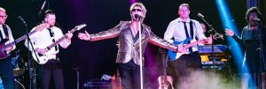 Rob Stewart, Gold jacket, sunglasses, microphone, purple lights, band members