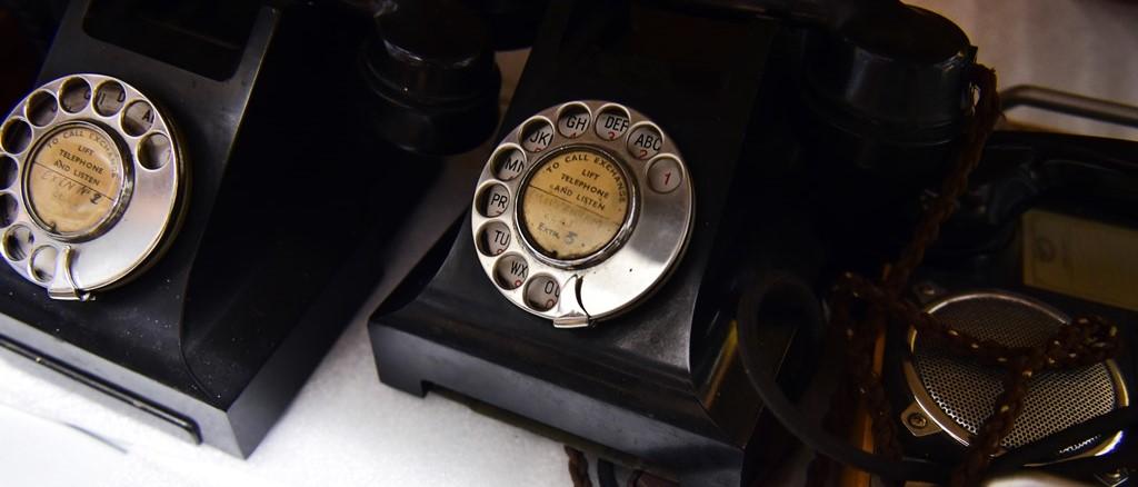 two bakelite telephones on a white shelf