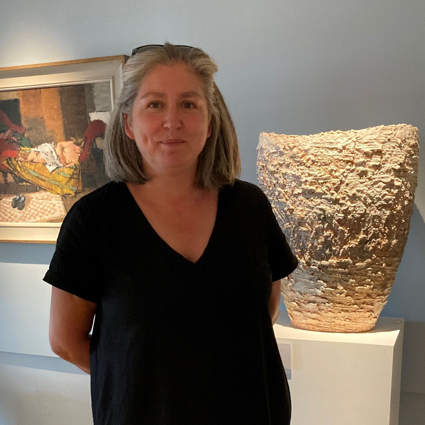 Woman, standing in front of a ceramic sculpture and a oil painting