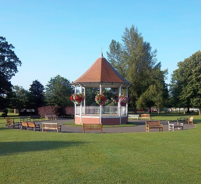 Green grass and blue sky with the white and orange bandstand in the middle. Several wooden benches dotted in a circle around the bandstand.