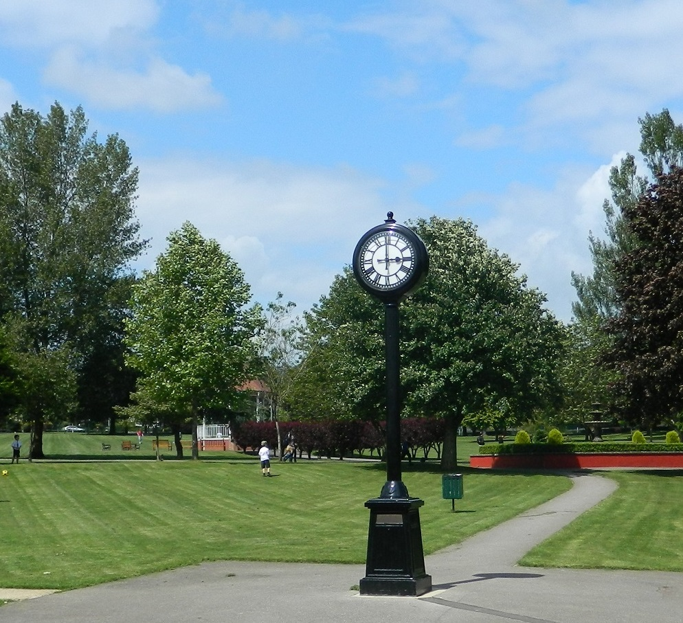 grey path with a black clock in the middle, green grass and blue skies surrounding.