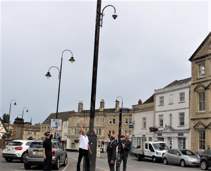 representatives from Wiltshire Council, Wiltshire Police and Chippenham Town Council all standing pointing at the new CCTV camera at the top of a lamp post in the town centre
