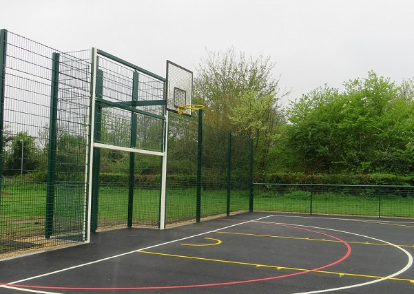 green fence with muti use games area inside including grey tarmac and white and yellow basketball hoop
