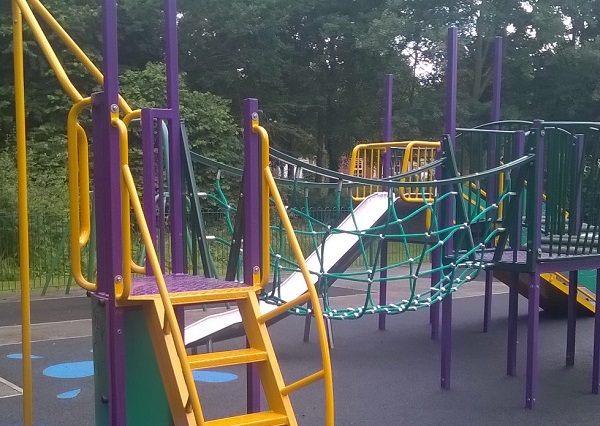 A yellow and purple climbing frame in a play park