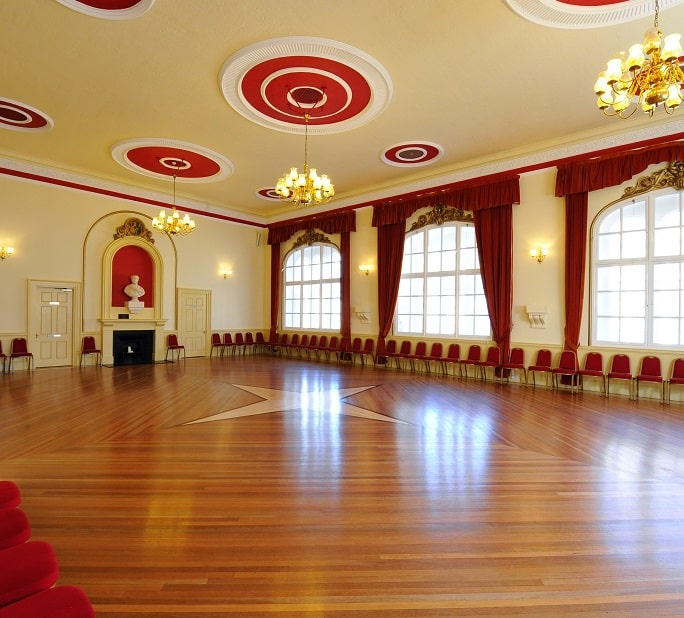 Chippenham Town Hall with red chairs lining the edge of the room, wooden floors, white ceiling with a chandelier hanging from the middle
