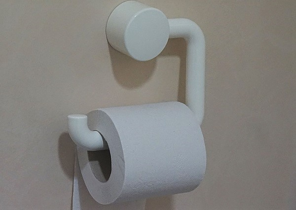light grey wall with a white toilet roll holder attached and a toilet roll on the toilet roll holder