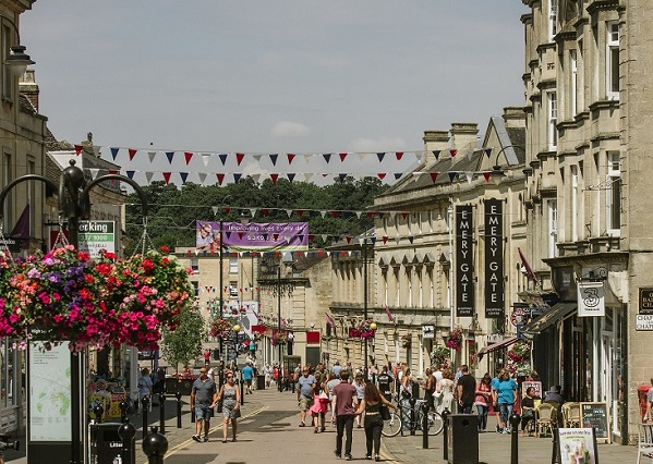 Chippenham High Street with several people walking around. Bright and vibrant hanging baskets line the street and black red and white bunting is tied between buildings that line the high street