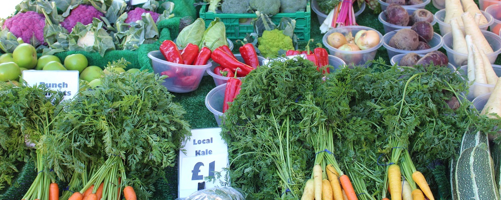 Fruit and veg stall at Chippenham Market with produce available including: orange & yellow carrots, green marrows, white and purple cauliflowers, red peppers.
