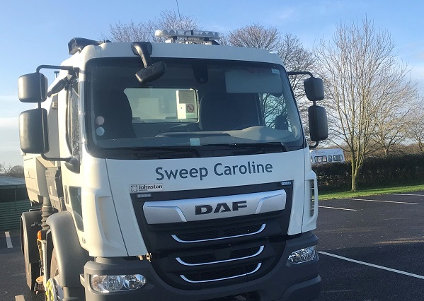 A white road sweeper parked on tarmac with the words 'Sweep Caroline' printed on the front.