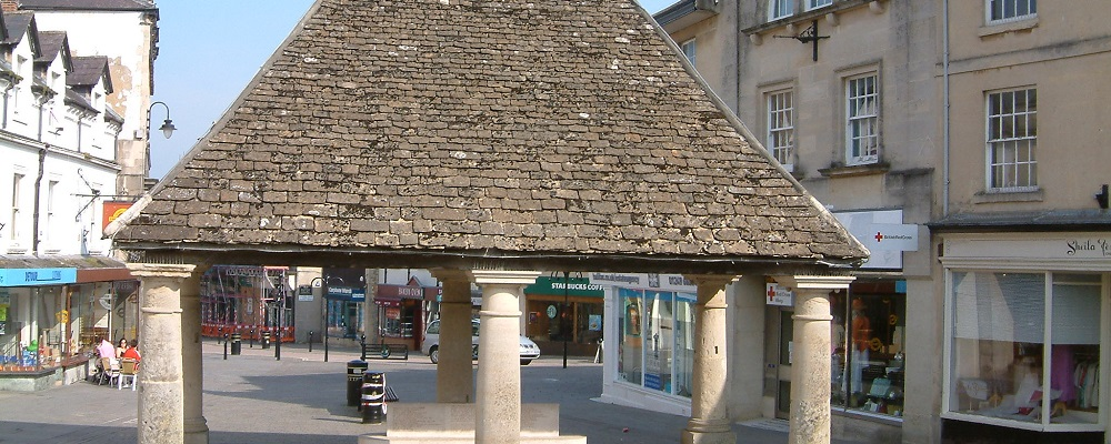 The Buttercross located on The High Street in Chippenham. A dark tile roof with a 6 lighter stone pillars beneath holding it up.