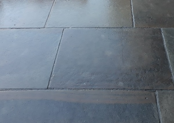 Dark grey and wet patio slabs clean from chewing gum removal