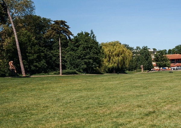 Monkton Park, a large patch of green grass with the Olympiad Leisure Centre in the background. Bright blue skies and vibrant green trees can also be seen.