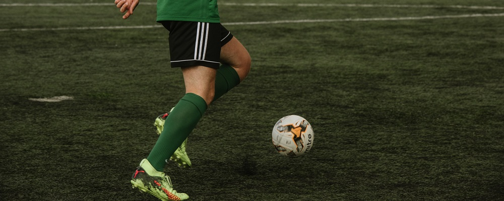 A young man kicking a white and orange football on green AstroTurf in black shorts with three white stripes down the side, dark green socks and florescent yellow football boots.