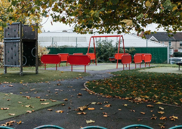 Play park with red swings located in the middle