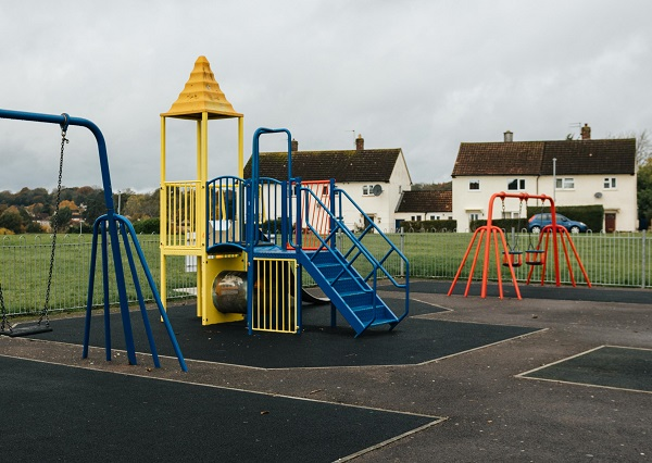 A mixture of blue, yellow and red climbing frames in a play park