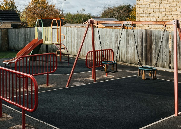 A red climbing frame with yellow and blue swings and red slide on grey tarmac