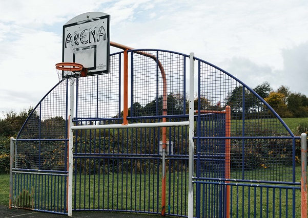 An orange basketball hoop, which is attached to a white, blue and orange multiuse frame