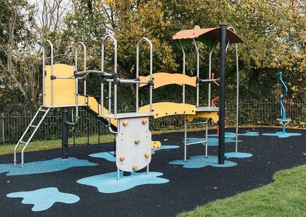 A yellow climbing frame on grey tarmac and painted light blue patches for colour