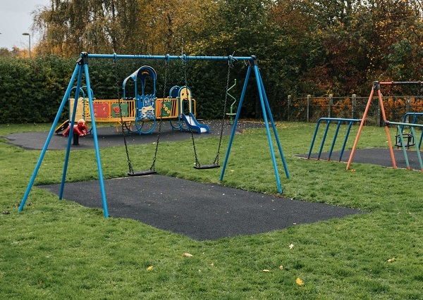 Blue swing set in the middle of a play park surrounded by green grass