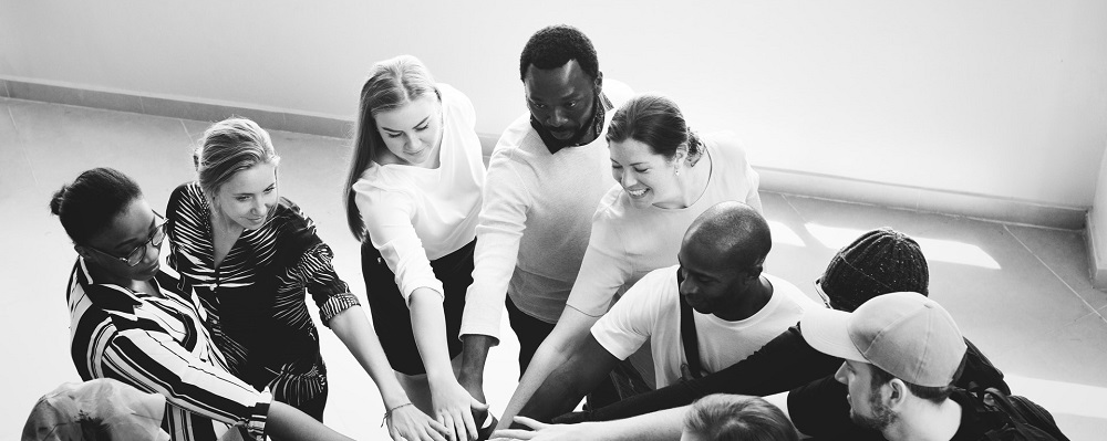 A black and white image with multiple people putting their hands in the middle of a circle