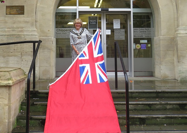 Mayor of Chippenham Councillor Teresa Hutton holding the Red Ensign flag on the Town Hall steps