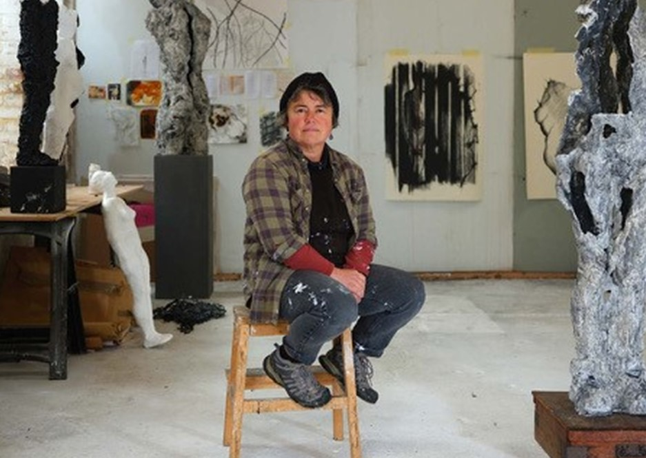 Artist sat on chair in studio space surrounded by artwork