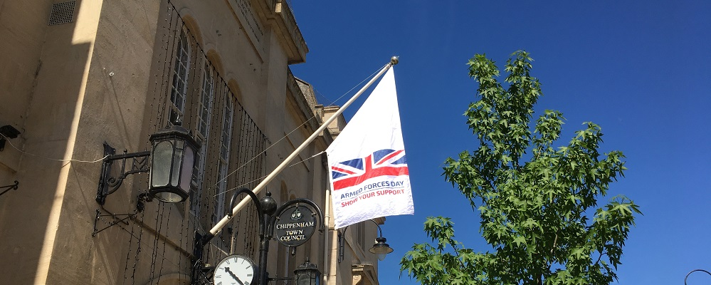 Armed Forces Day flag flown at the Town Hall which reads 'Armed Forces Day, show your support' in blue and red writing on a white flag