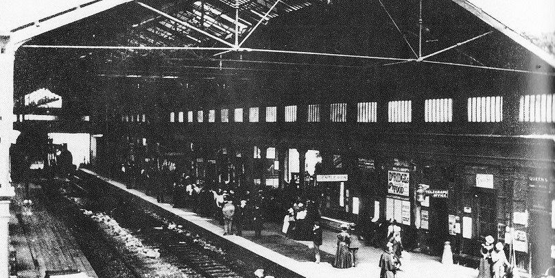 Black and white photograph taken looking down onto the station with tracks and platforms visible. There are crowds of people in Victorian dress on one platform. Both platforms are enclosed by one canopy. A train is just entering the station