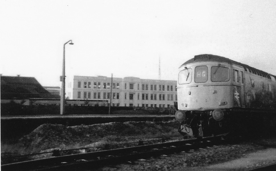 black and white photograph of diesel train at station with large white building in background