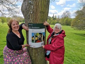two women stood next to a tree holding an art outdoors banner in a park