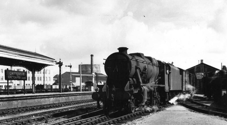 black and white photograph of steam train at station with sign visible chippenham junction for calne. A shed is visible behind the train