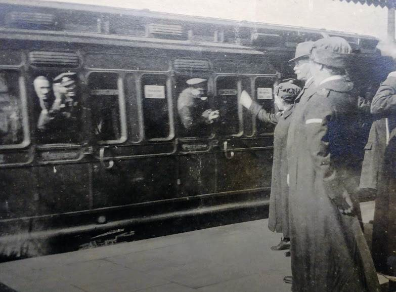 Black and white photograph of nurses in long coat uniforms waving at a moving train with men smiling and waving out of the windows.