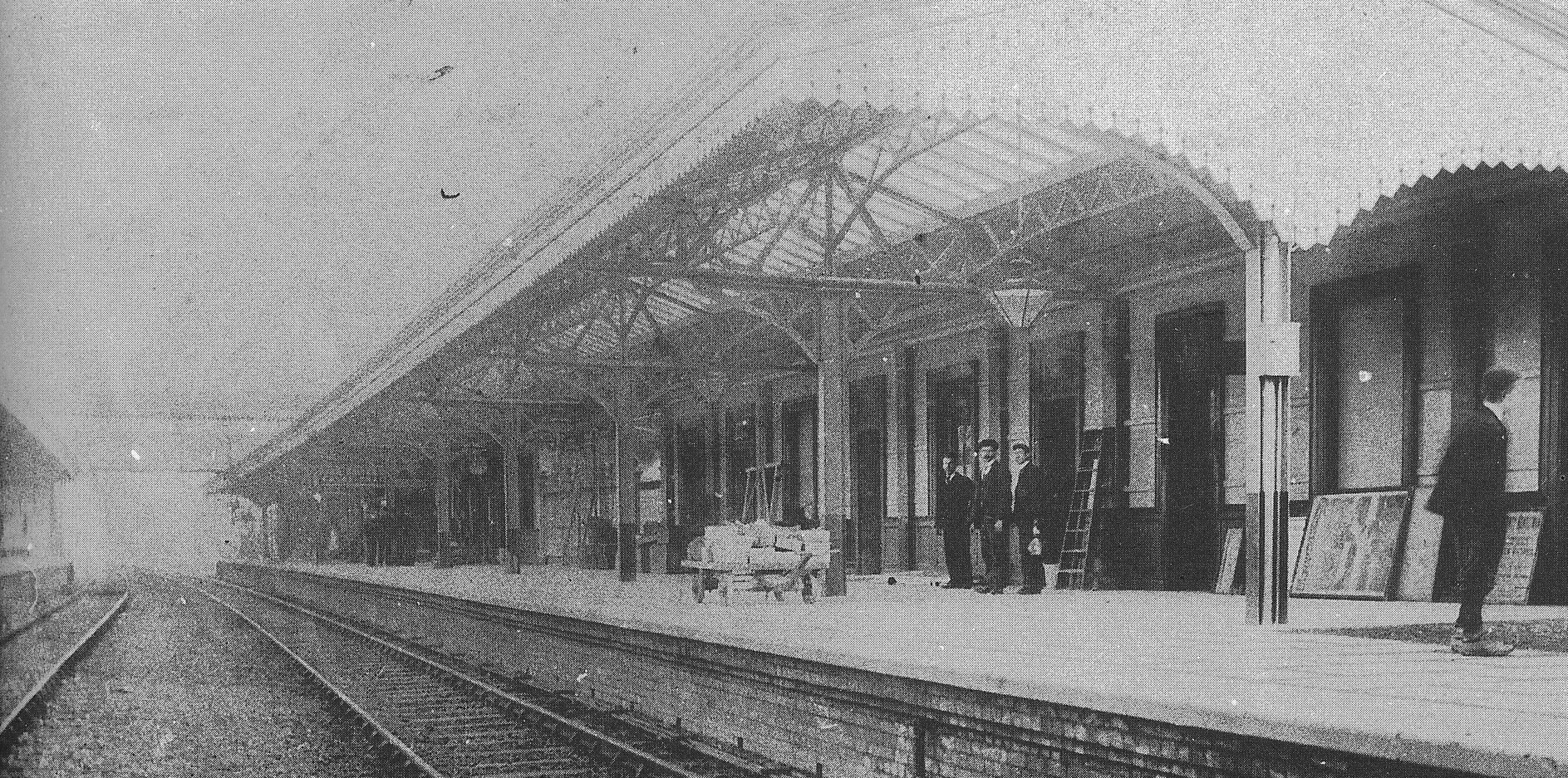 Black and white photograph taken from the tracks with platforms either side. There are four men on the platform looking at the camera. Each platform has an individual canopy