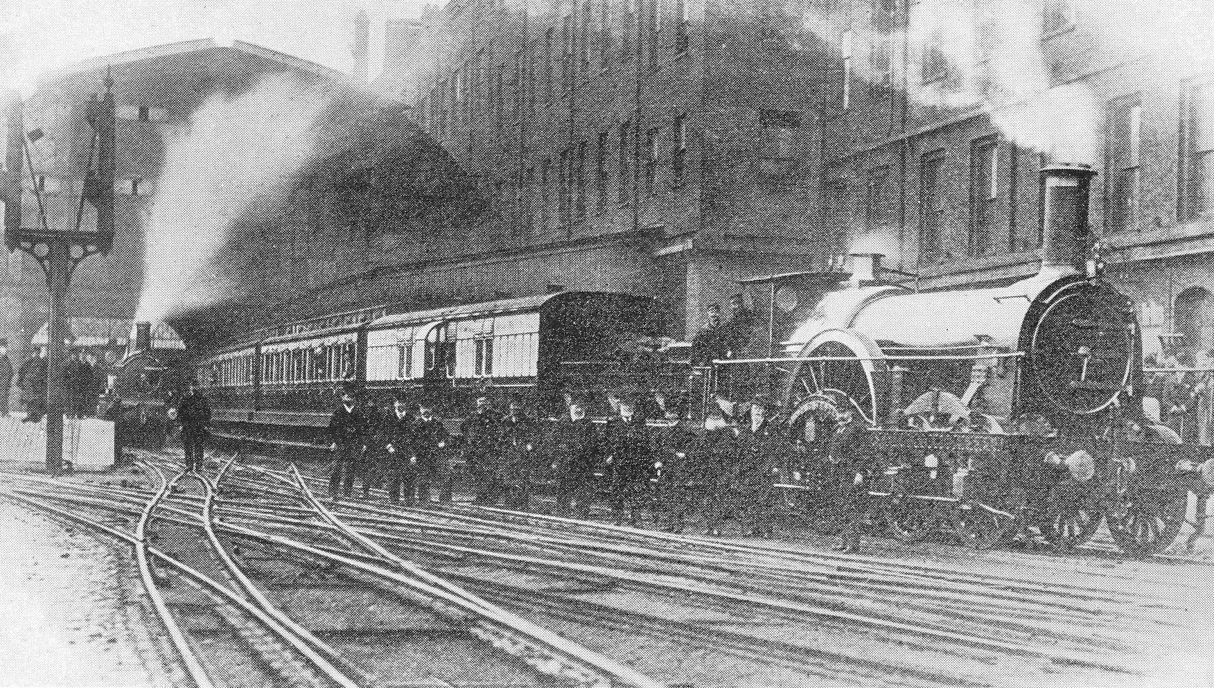 Black and white photograph of steam train outside a large station with many tracks visible and a building of multiple stories behind it. There are at least 12 men stood infront of the train, and two men in the cab of the engine.