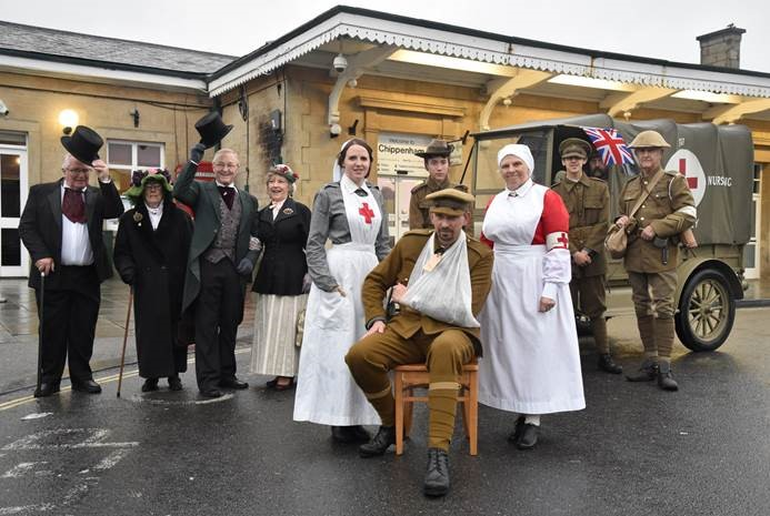 Color photograph of re-enactors infront of Chippenham Station ticket office including a wounded solider, two nurses and smartly dressed townspeople. There is also a vehicle from the era